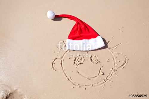 Drawn santa hat funny Smiley in the sand drawn